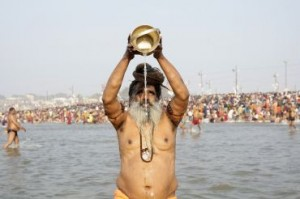 "A Sadhu prays after taking in waters of river Ganges during second ritual bathing on occasion of Paush Purnima at ongoing ""Kumbh Mela"", or Pitcher Festival, in Allahabad"